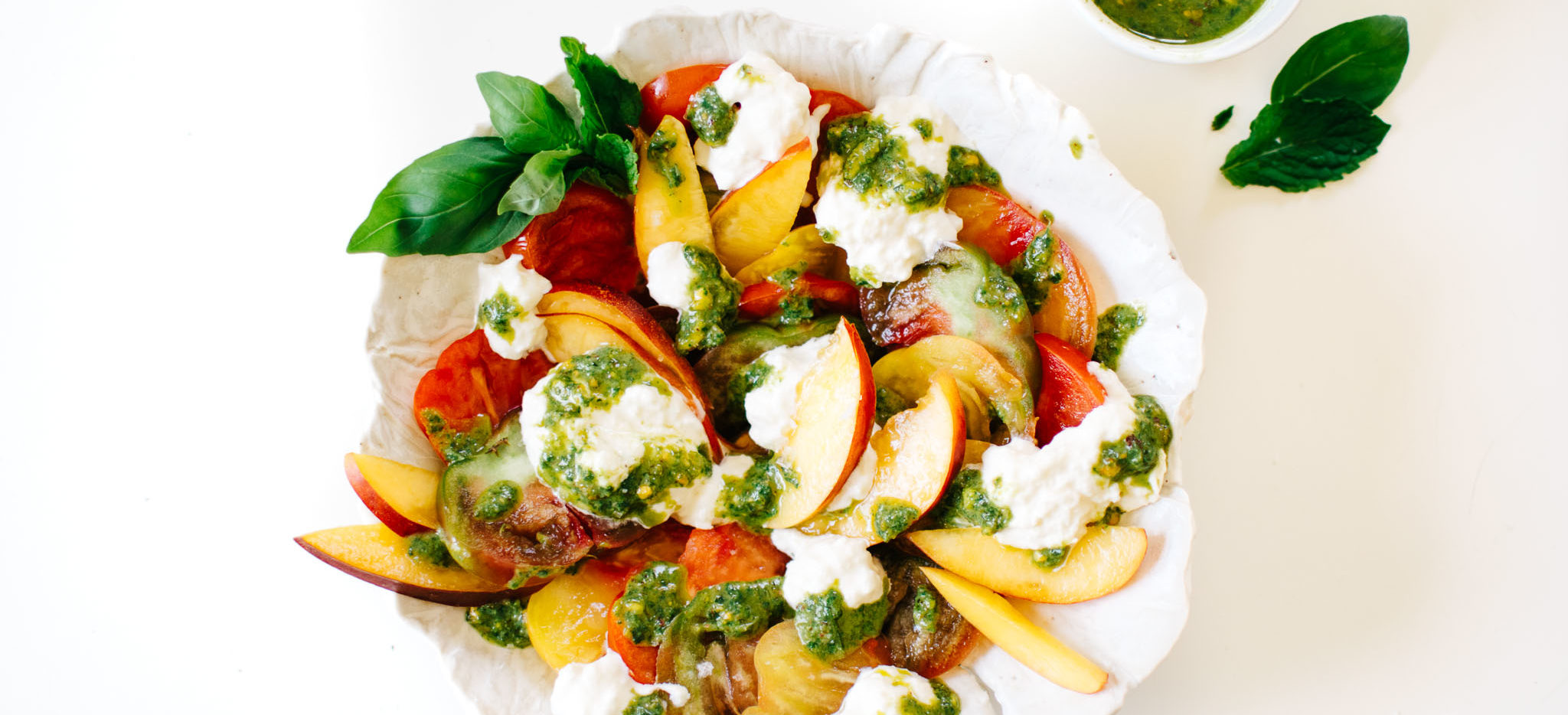 HEIRLOOM TOMATO, NECTARINE & BURRATA CAPRESE SALAD WITH PISTACHIO PESTO.